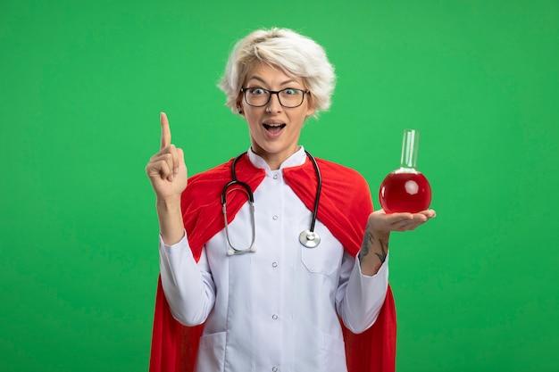 赤い岬と光学ガラスの聴診器で医者の制服を着た驚いたスラブのスーパーヒーローの女性は、ガラスフラスコに赤い化学液体を保持し、コピースペースで緑の壁に隔離された上向き