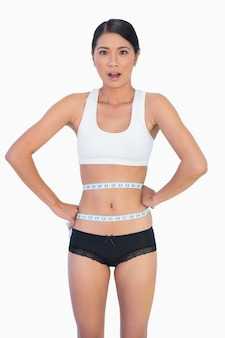 Surprised slim woman measuring her waist