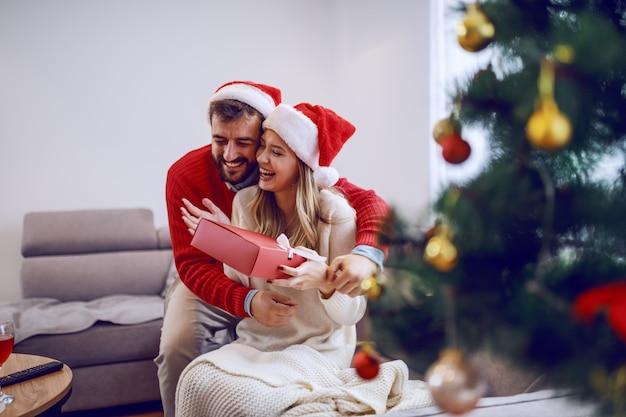 Удивленная усмехаясь кавказская женщина сидя на софе в живущей комнате и держа подарок. мужчина обнимает женщину. у обоих шляпы санта на головах. на переднем плане елки. интерьер гостиной.