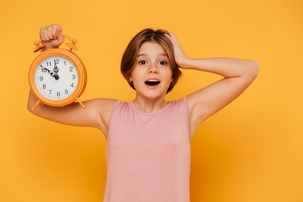 Surprised smiling girl showing alarm clock and holding her head isolated