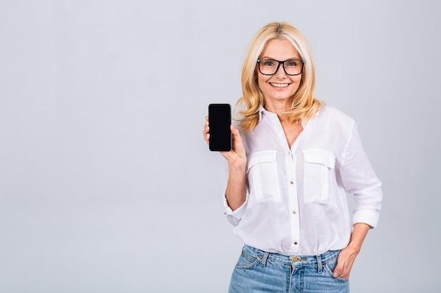 白灰色の背景に分離されたカメラを見ながら、カジュアルに空白のスマートフォンの画面を表示して、幸せなシニア成熟した女性の笑顔に驚いた。電話を使う。