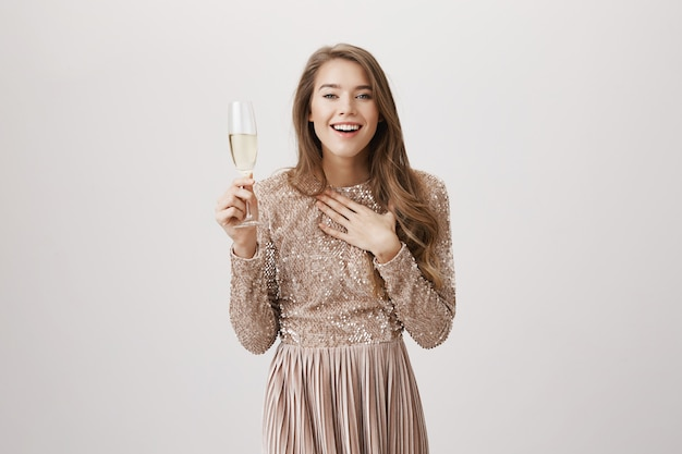 Surprised smiling woman in evening dress, drinking champagne