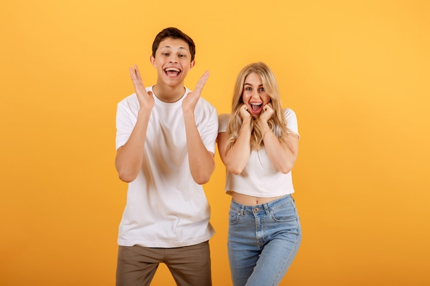 Surprised smiling young couple, two friends guy and girl in white t-shirts are posing on yellow orange background.