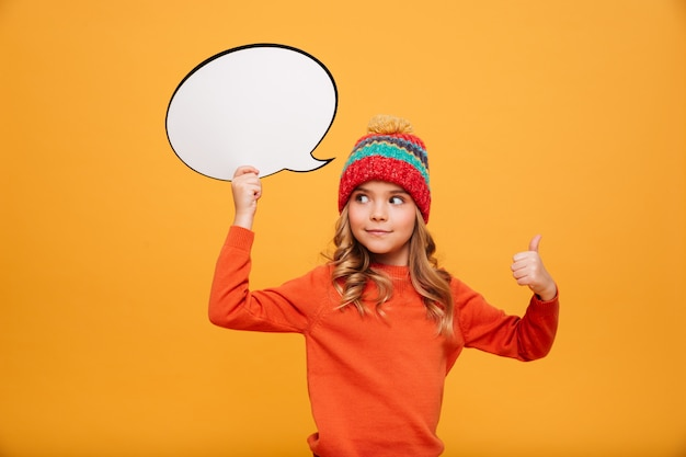 Surprised smiling young girl in sweater and hat holding blank speech bubble and showing thumb up while looking away over orange