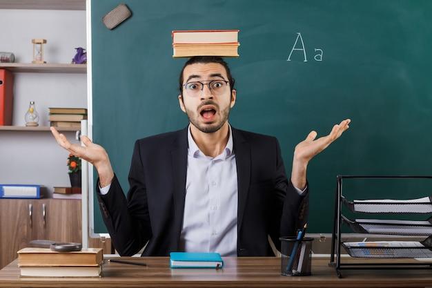 Sorpreso che allarga le mani insegnante maschio con gli occhiali che tiene un libro sulla testa seduto al tavolo con gli strumenti della scuola in classe