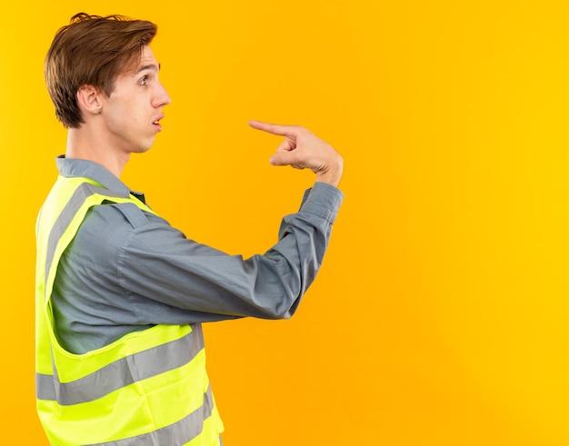 프로필 보기에 놀란 서 있는 젊은 건축업자 남자는 제복을 입고 자신을 가리킵니다.