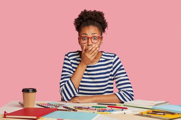 ピンクの壁に向かって机でポーズをとって驚いた学生の女の子