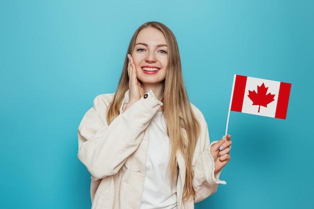笑顔で小さなカナダの旗を持ってカメラを見て驚いた学生の女の子