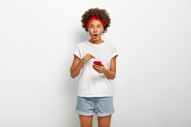 У удивленного студента вьющиеся волосы, он указывает на смартфон, делает покупки в интернете, удивлен большой ценой на что-то