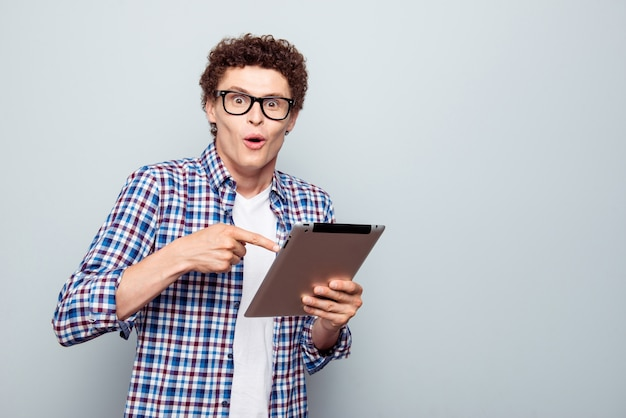 Surprised student man guy in glasses holding tablet points at screen finger
