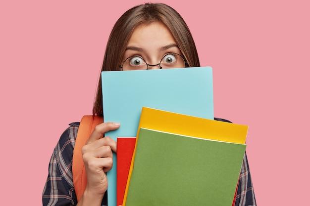 Studente sorpreso in posa contro il muro rosa con gli occhiali