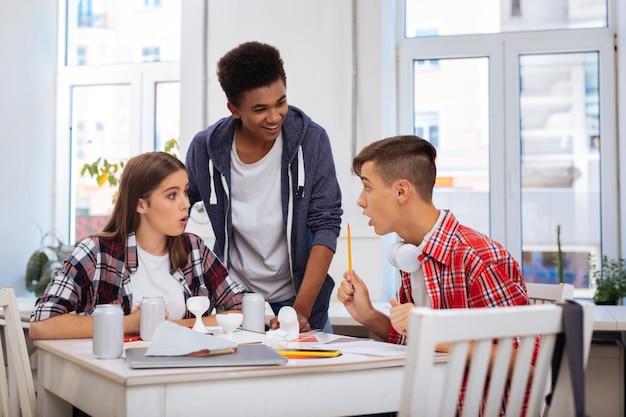 놀란 학생. 시험 결과를보고 정말 놀란 세 명의 잘 생긴 현대 학생