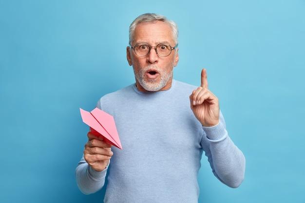 驚いた唖然としたひげを生やした成熟した灰色の髪の男は人差し指を指さし、紙飛行機を保持し、口を開いたままにし、眼鏡をかけ、青いスタジオの壁に対してジャンパーポーズをとる