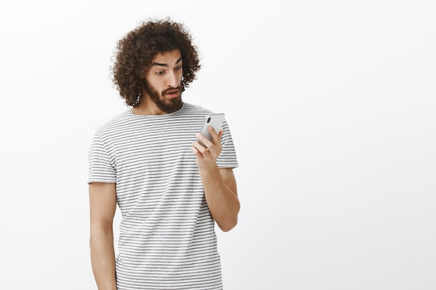 Surprised stunned emotive guy with curly hair and beard, staring at smartphone screen with amazed expression