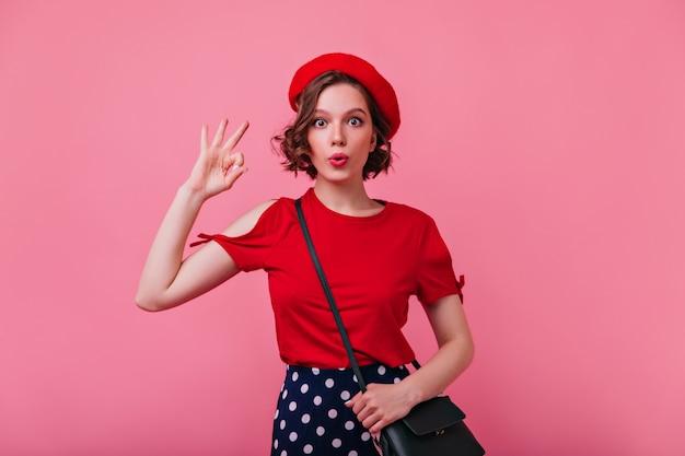 赤いtシャツの面白いポーズで驚いた見事な女の子。驚いた感情を表現するベレー帽の壮大な女性モデルの屋内ショット。