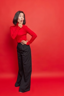Surprised stylish dark haired asian woman looks back with shocked expression wears turtleneck and loose black trousers poses against vivid red wall copy space for your promotional content