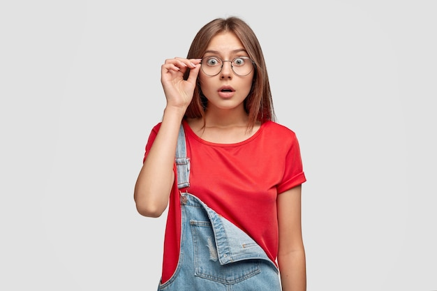 Surprised stylish teenager in casual red t shirt and denim overalls, keeps hand on rim of spectacles
