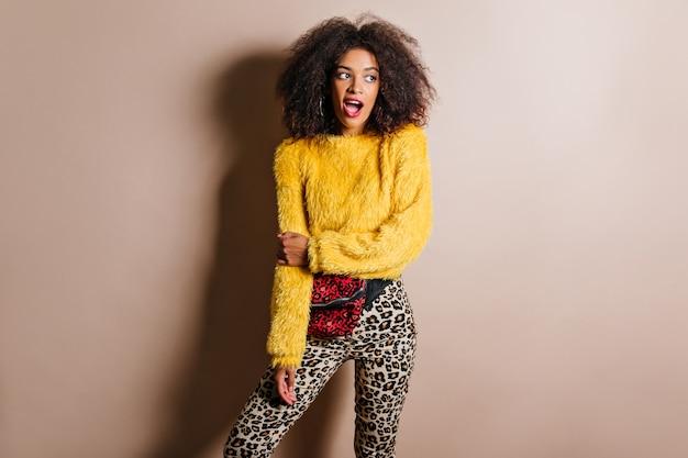 Surprised stylish woman in earrings posing on brown wall