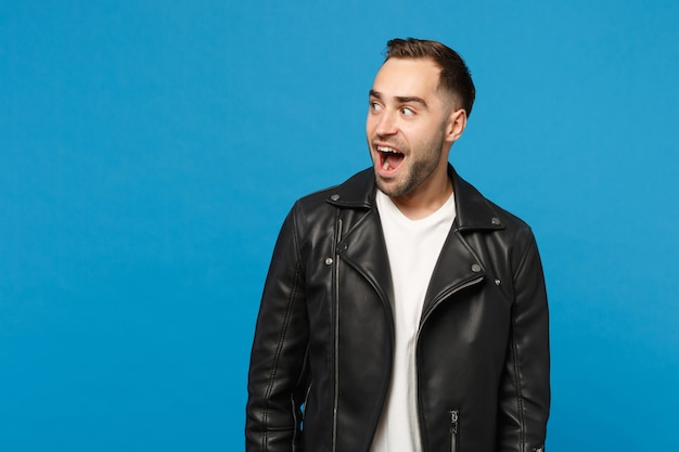 Surprised stylish young bearded man in black leather jacket white t-shirt looking aside isolated on blue wall background studio portrait. people sincere emotions lifestyle concept. mock up copy space.