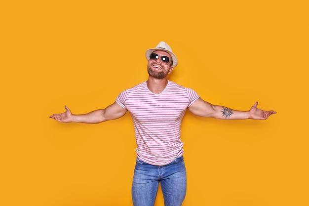 선글라스와 여름 밀짚 모자를 쓴 놀란 성공한 청년이 손을 크게 벌리고 비명을 지르며...