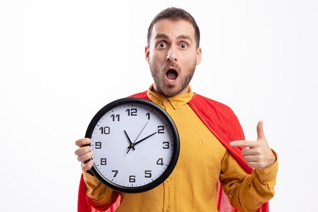 Удивленный человек супергероя в красном плаще держит и указывает на часы, изолированные на белой стене