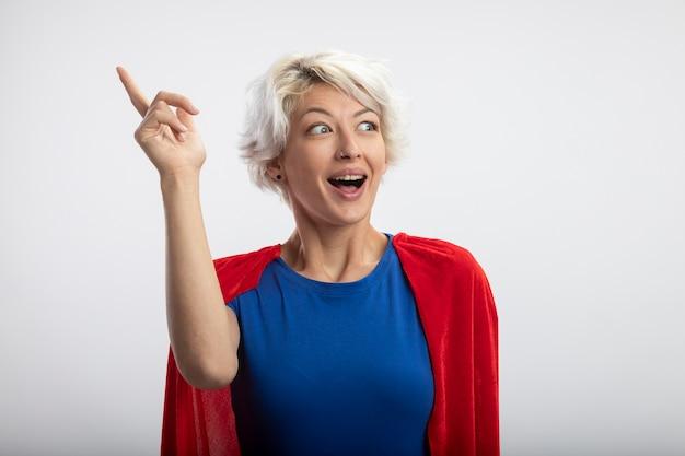 Superwoman sorpresa con mantello rosso rivolto verso l'alto e guardando il lato isolato sul muro bianco