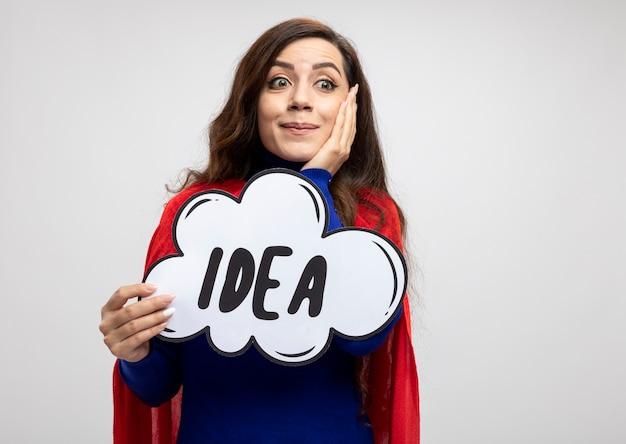 赤いマントで驚いたスーパーウーマンは顔に手を置き、白い壁で隔離された側を見てアイデアバブルを保持します