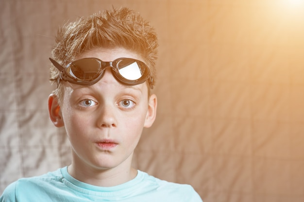 Surprised teen boy in swimming glasses