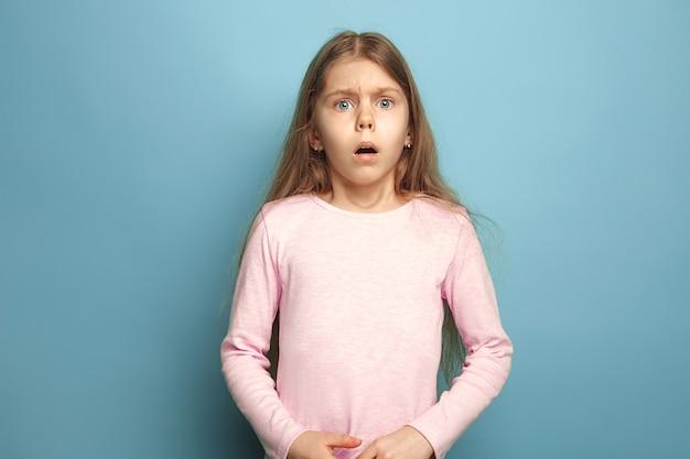 Ragazza teenager sorpresa su sfondo blu studio. le espressioni facciali e le emozioni delle persone concetto. colori alla moda.