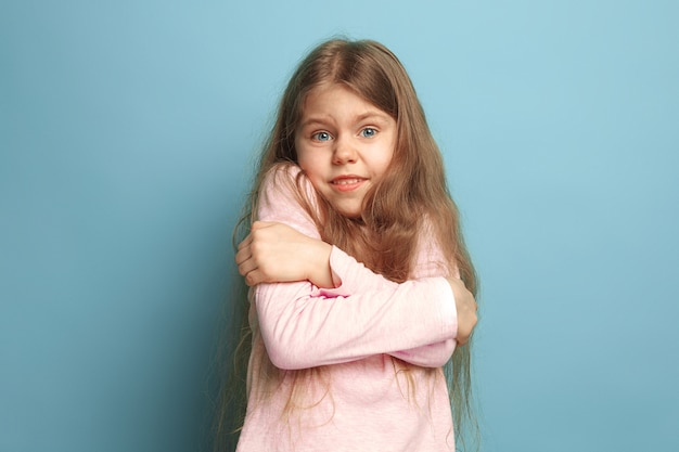 Ragazza teenager sorpresa su sfondo blu studio. le espressioni facciali e le emozioni delle persone concetto.