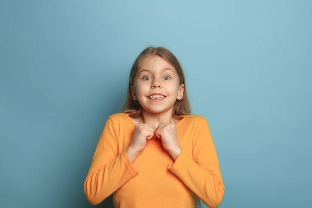 青いスタジオの背景に驚いた十代の少女。顔の表情と人々の感情の概念。