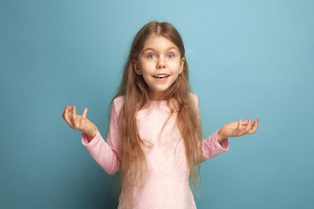 Удивленная девочка-подросток на синем фоне студии. выражения лица и концепция эмоций людей.