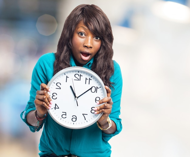 Surprised teen showing a clock