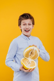 Surprised teenage boy looking at camera while holding cut into half large grapefruit