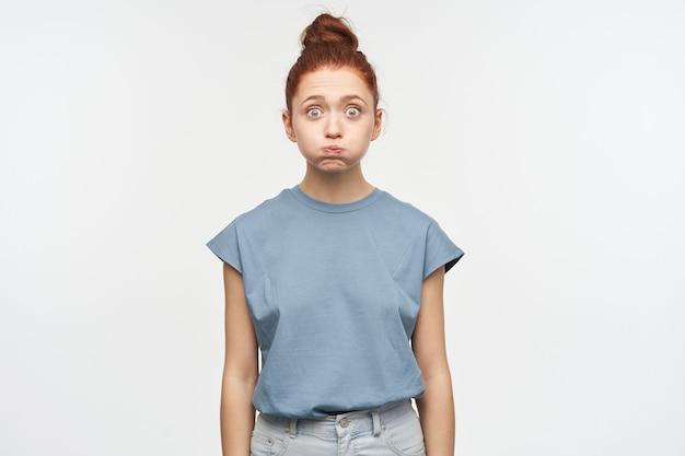 Adolescente sorpresa, donna dall'aspetto divertente con i capelli rossi raccolti in un panino. indossare jeans e maglietta blu. le gonfiò le guance. isolato su muro bianco