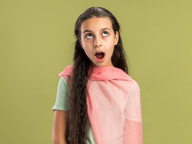 복사 공간이 있는 올리브 녹색 벽에 격리된 입을 벌리고 올려다보는 목도리를 입은 10대 소녀