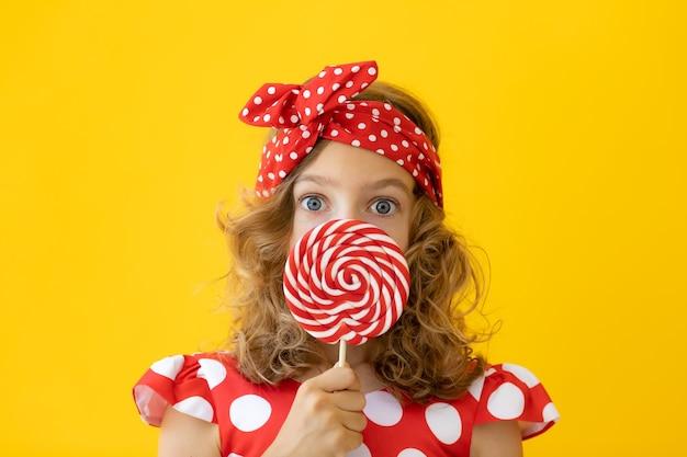 노란색 벽에 빨간 막대 사탕을 들고 놀된 십 대 소녀