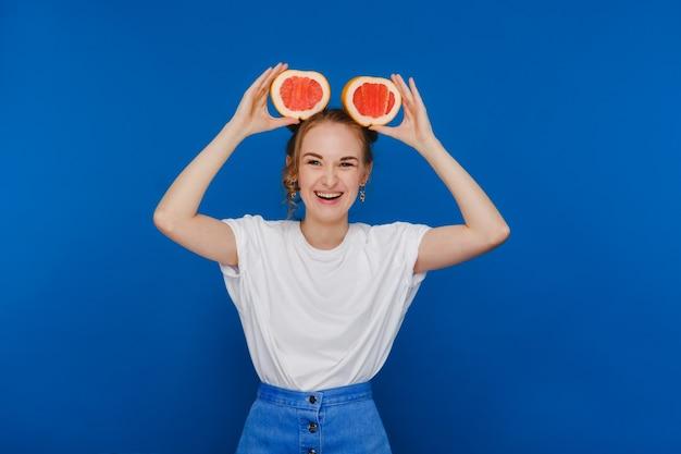Удивленная смеющаяся девушка держит грейпфрут, как уши. веганский образ жизни. улыбающаяся женщина, еда концепции. диета органическая, потеря веса и здоровое питание. смузи и свежий сок.