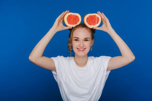 Удивленная смеющаяся девушка держит грейпфрут, как уши.