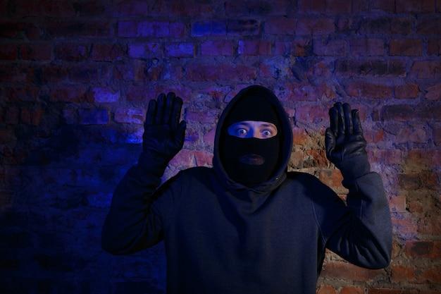 벽돌 벽에 손을 들고 서 있는 놀란 도둑