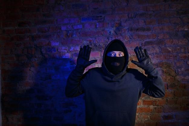 벽돌 벽에 팔을 들고 서 있는 놀란 도둑