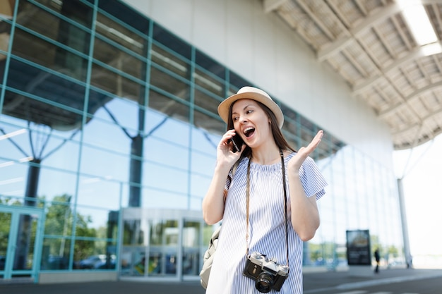 Surprised traveler tourist woman with retro vintage photo camera talk on mobile phone calling friend