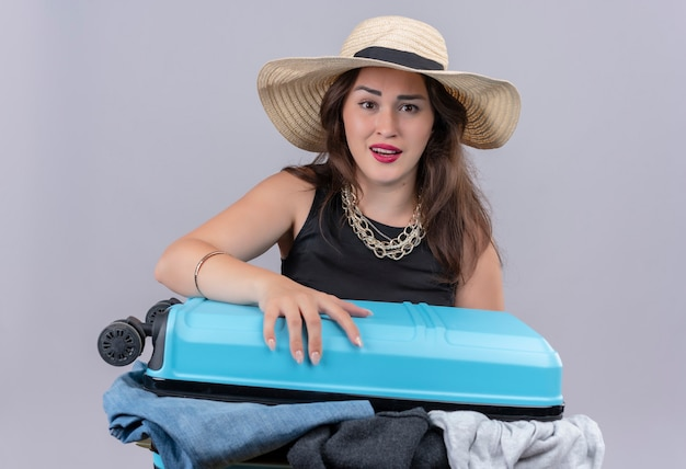 Surprised traveler young girl wearing black undershirt in hat holding open suitcase on white background