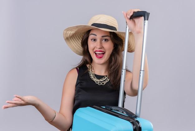 La ragazza sorpreso del viaggiatore che porta la maglietta nera in cappello ha messo la sua mano sulla valigia su priorità bassa bianca