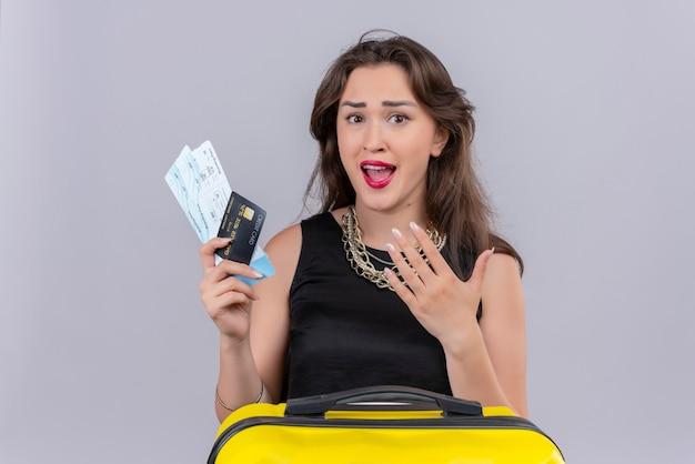 白い背景の上のチケットとクレジットカードを保持している黒のアンダーシャツを着て驚いた旅行者少女