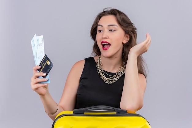 Удивленная путешественница молодая девушка в черной майке держит билеты и положила руку на чемодан на белом фоне