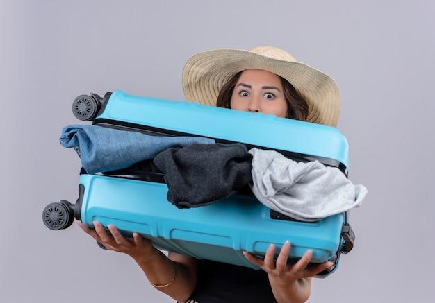 Удивленный путешественник молодая девушка в черной майке в шляпе держит открытый чемодан на белом фоне