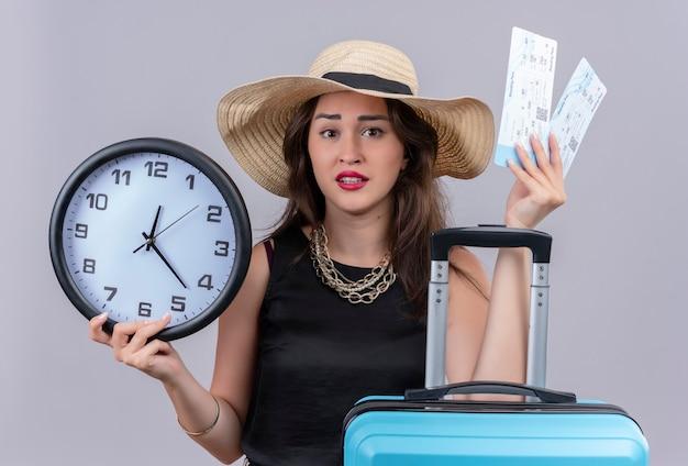 Удивленная путешественница молодая девушка в черной майке в шляпе держит чемодан и билеты на белом фоне