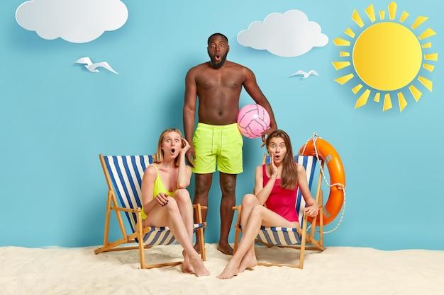 Surprised two women in bathingsuit, sit on deckchairs, dark skinned man stands near, wears green shorts