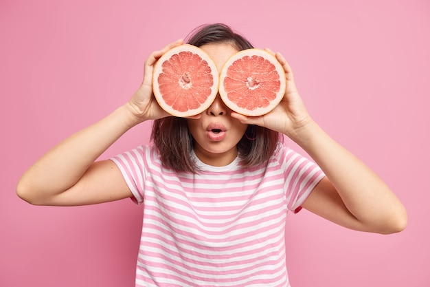 Surprised unrecognizable woman covers eyes with two big halves of grapefruit eats healthy food containing much vitamins wears striped t shirt isolated over pink wall tries to lose weight